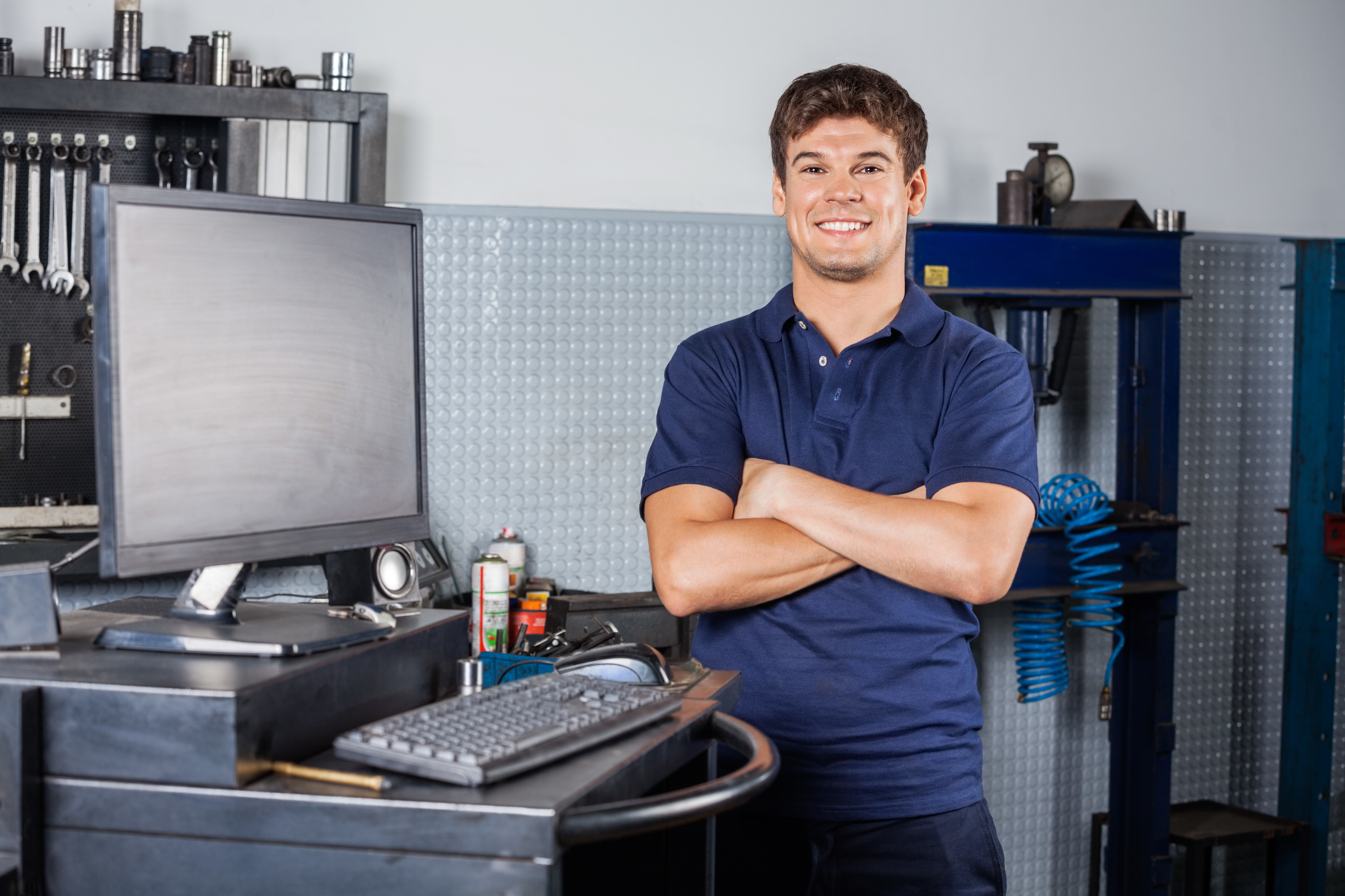 Portrait of confident male technician standing arms crossed by computer in auto repair shop